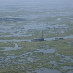 Wetlands and oil rig.  Photo Credits: Lynn Miller