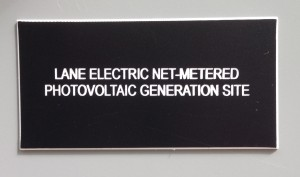 Plaque reading Lane Electric net-metered photovoltaic generation site