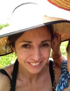 Close up portrait of Francisca in a sunhat with a toddler pulling on her ear.