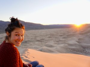 IWRC staff member Aya in a red sweater sitting on a dune in sunllight